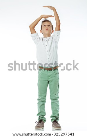 Happy boy growing up to be tall leaning against the wall - stock photo