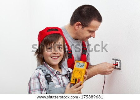 Happy boy helping his father mounting electrical wall fixtures - holding the multimeter - stock photo