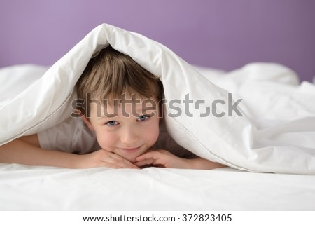 Happy boy hiding in bed under a white blanket or coverlet. Boy at bed. Child in bed