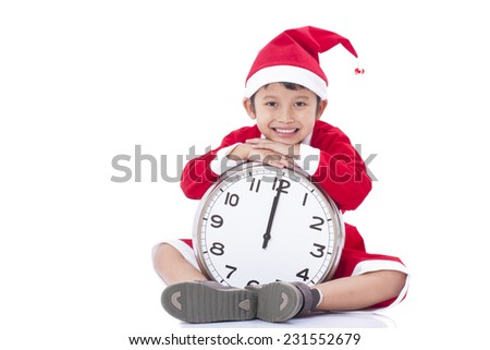 Happy boy holding a big clock at christmas