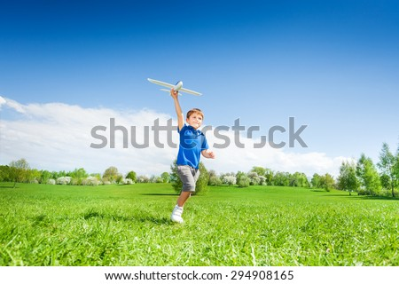 Happy boy holding airplane toy during running - stock photo
