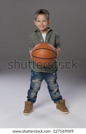 Happy boy holding  basketball ball in hand  - stock photo