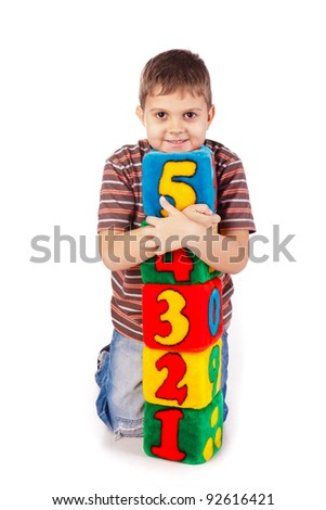Happy boy holding blocks with numbers over white background - stock photo