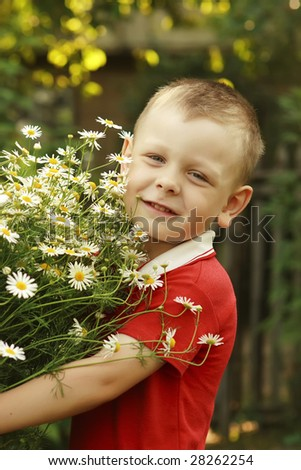 Happy boy holding bouquet of camomiles - stock photo