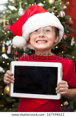 Happy boy holding digital tablet at Christmas time  - stock photo