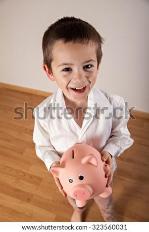 Happy boy holding his piggy bank - stock photo
