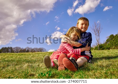 Happy boy hugging girl sitting together on grass - stock photo