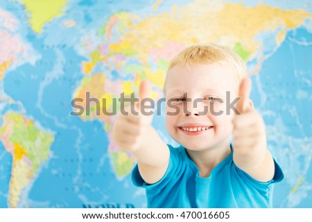 Happy boy in a classroom of geography showing thumbs up
