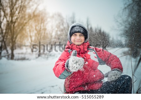 happy boy in a snowdrift sits and laughs
