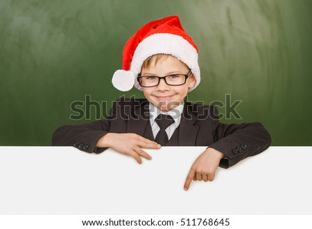 Happy boy in a suit with red christmas hat pointing down at blank billboard