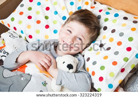 Happy boy in bed. - stock photo