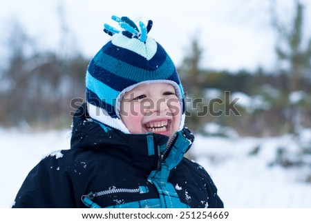 Happy boy in blue clothes in snowing winter outdoor - stock photo