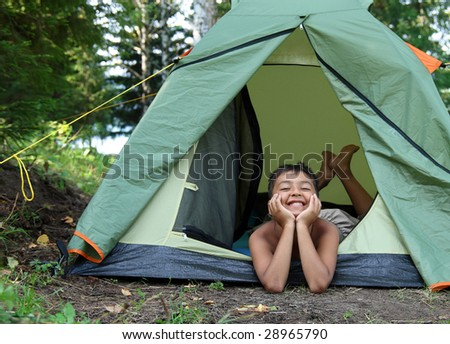 happy boy in camping tent in summer forest - stock photo