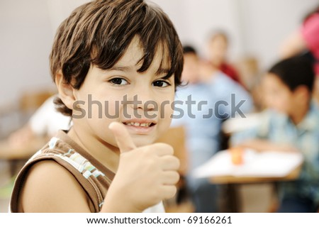 Happy boy in classroom with thumb up - stock photo