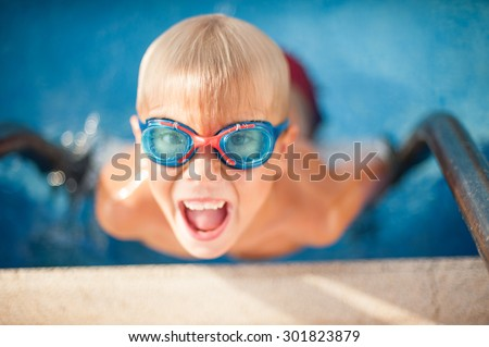 Happy boy in glasses of water swims in the pool - stock photo