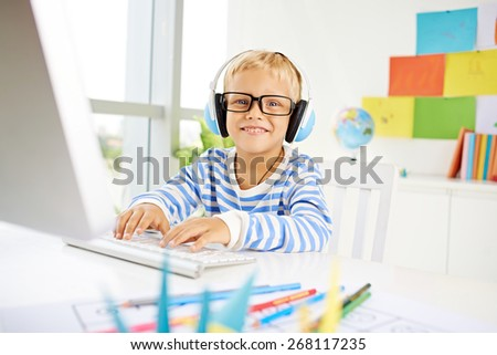 Happy boy in glasses playing on computer