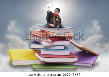 Happy boy in graduation suit sitting on pile of books  - stock photo