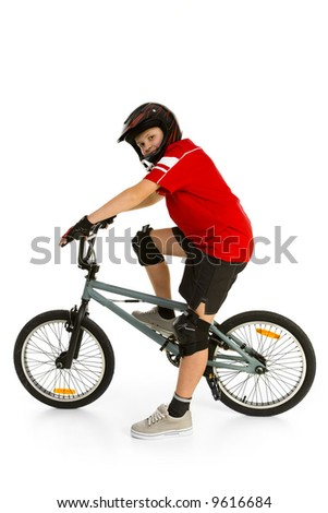 Happy boy in helmet on BMX and looking at camera. Side view. Isolated on white background. - stock photo