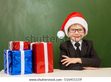 Happy boy in red christmas hat with gift boxes near empty green blackboard.