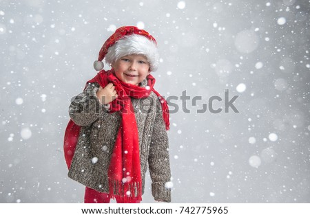 Happy boy in red xmas hat. Child with Xmas bag full of gifts and present. Buying christmas gifts - online shopping and delivery concept. Happy smiling boy with Santa costume. New Year and Christmas.