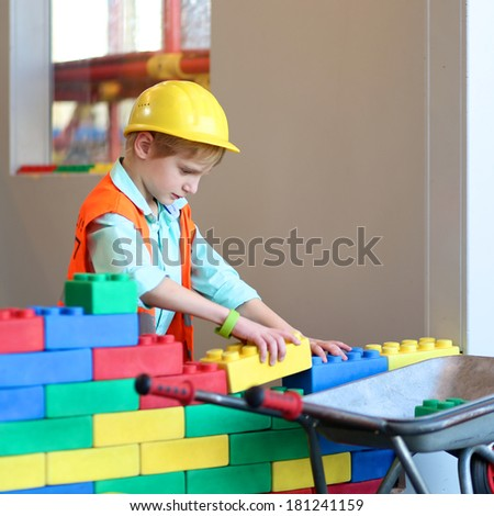 Happy boy in safety helmet and high visibility jackets playing indoors building a house with big plastic construction bricks - stock photo