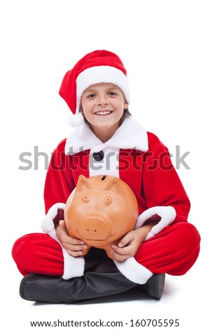 Happy boy in santa costume smiling and holding piggy bank - isolated