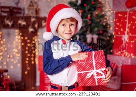 Happy boy in santa hat with a gift near the Christmas tree - stock photo