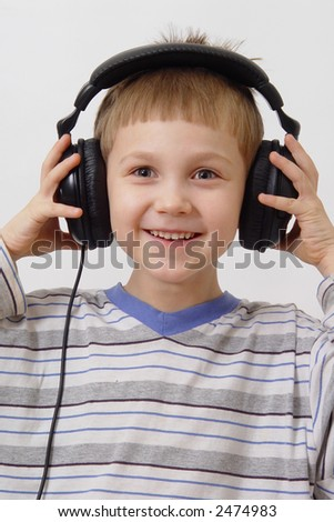 Happy boy in striped shirt, listenning music on  black headphones