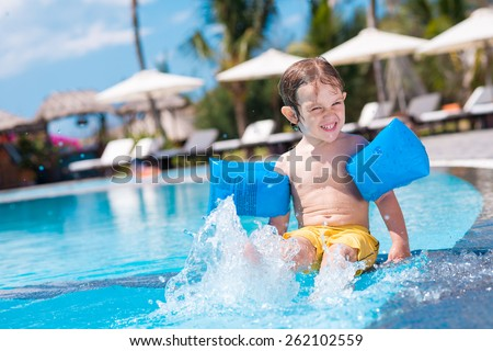 Happy boy in swimming armbands splashing in the pool - stock photo