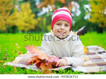 happy boy in the autumn park with yellow leaves in his hands