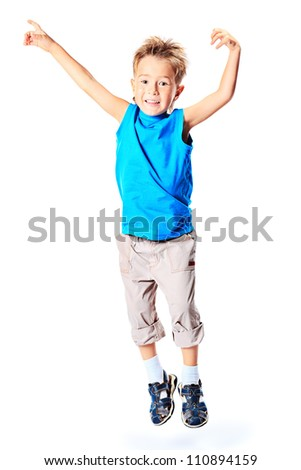 Happy boy is jumping at studio. - stock photo