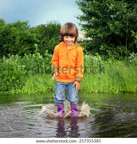 happy boy jump in puddle - stock photo