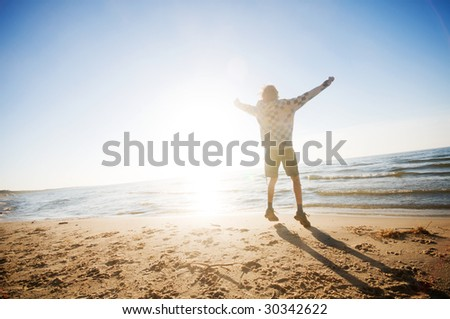 Happy boy jumping for joy at the beach - stock photo