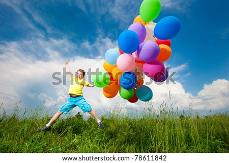 Happy boy jumpy on meadow with balloons - stock photo