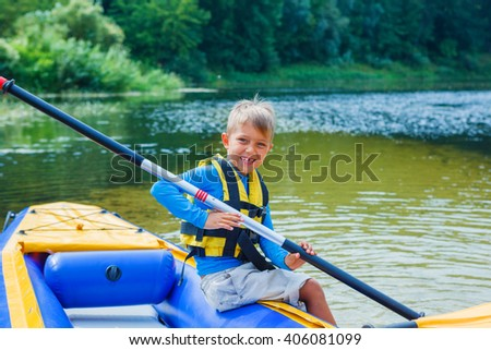 Happy boy kayaking on the river - stock photo