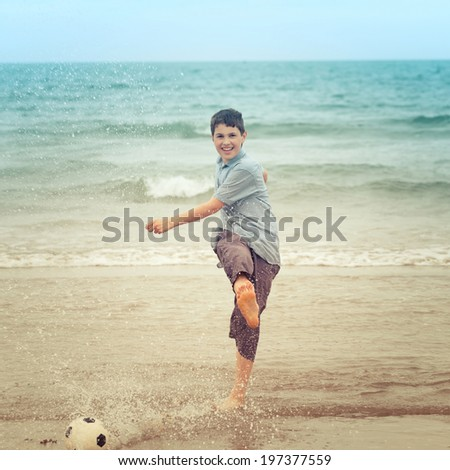 Happy boy kicking a football on the beach