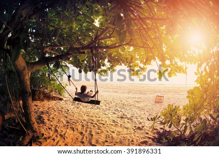 Happy boy kid on swing enjoy freedom and summer on sea shore on sunset - stock photo
