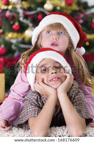 happy boy laughing in his sister embrace on Christmas evening  - stock photo