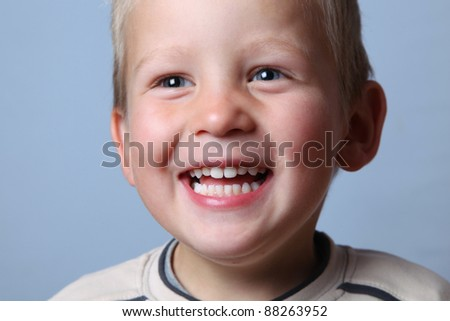 happy boy laughs and shows teeth