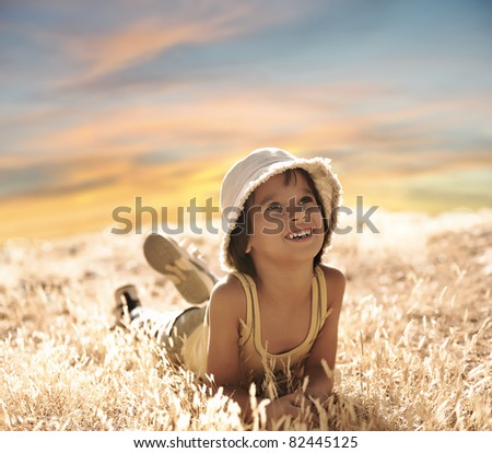 Happy boy laying on ground, yellow grass, summer to fall period - stock photo