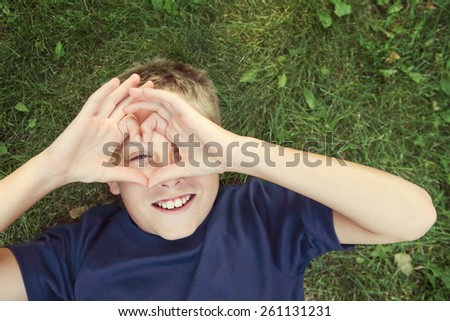 Happy boy laying outdoors making a heart shape with his hands. - stock photo