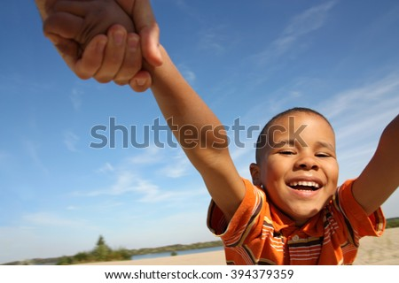 Happy boy. Little black boy playing on the beach, circling hand in hand.