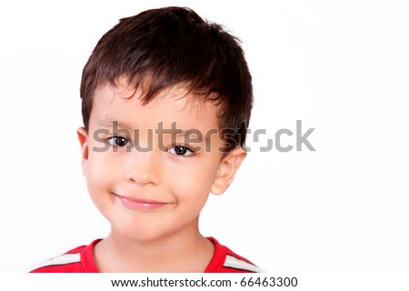 Happy boy looking at the camera with a small smile and hair on his face - stock photo