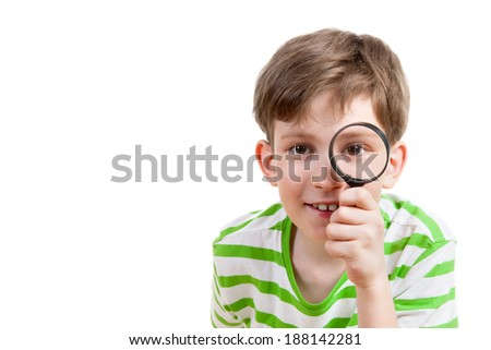 happy boy looking through a magnifying glass - stock photo