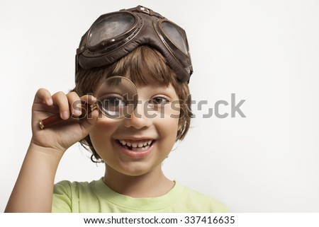 happy boy looking through a magnifying glass