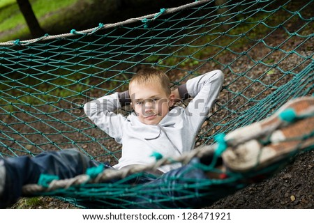 Happy boy lying on a hammock.