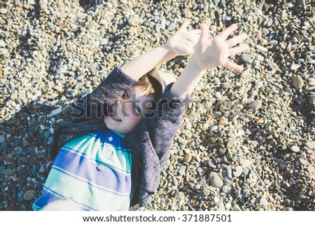 Happy boy lying on sand on the beach with his hands up