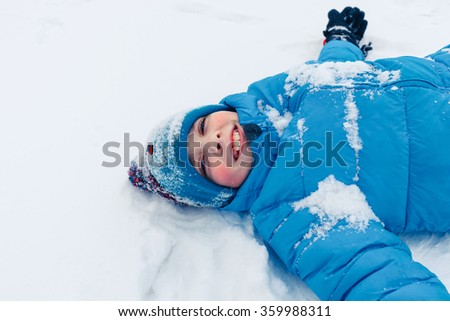 Happy boy lying on snow fur on the snow covered river at winter.  - stock photo