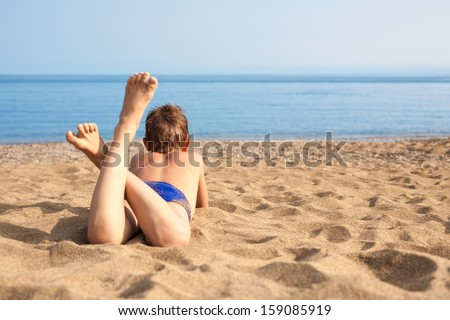 Happy boy lying on the beach and looking out to sea. Boy is nine years old. - stock photo