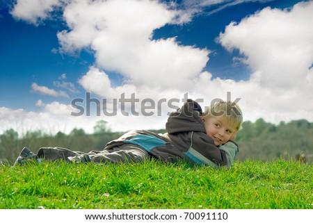 Happy Boy lying on the grass outdoors - stock photo